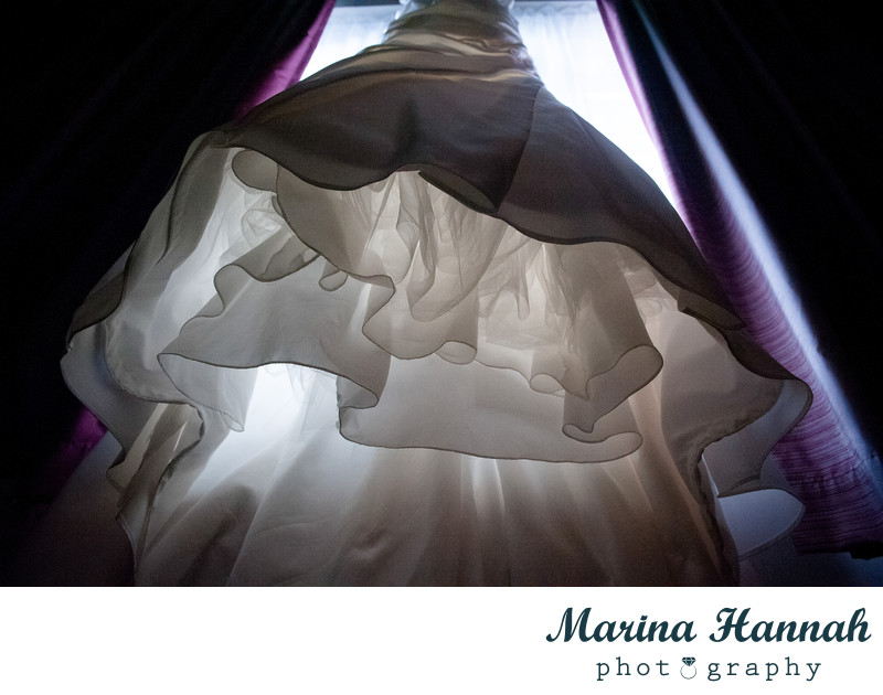 A photo of a wedding dress hanging on the window