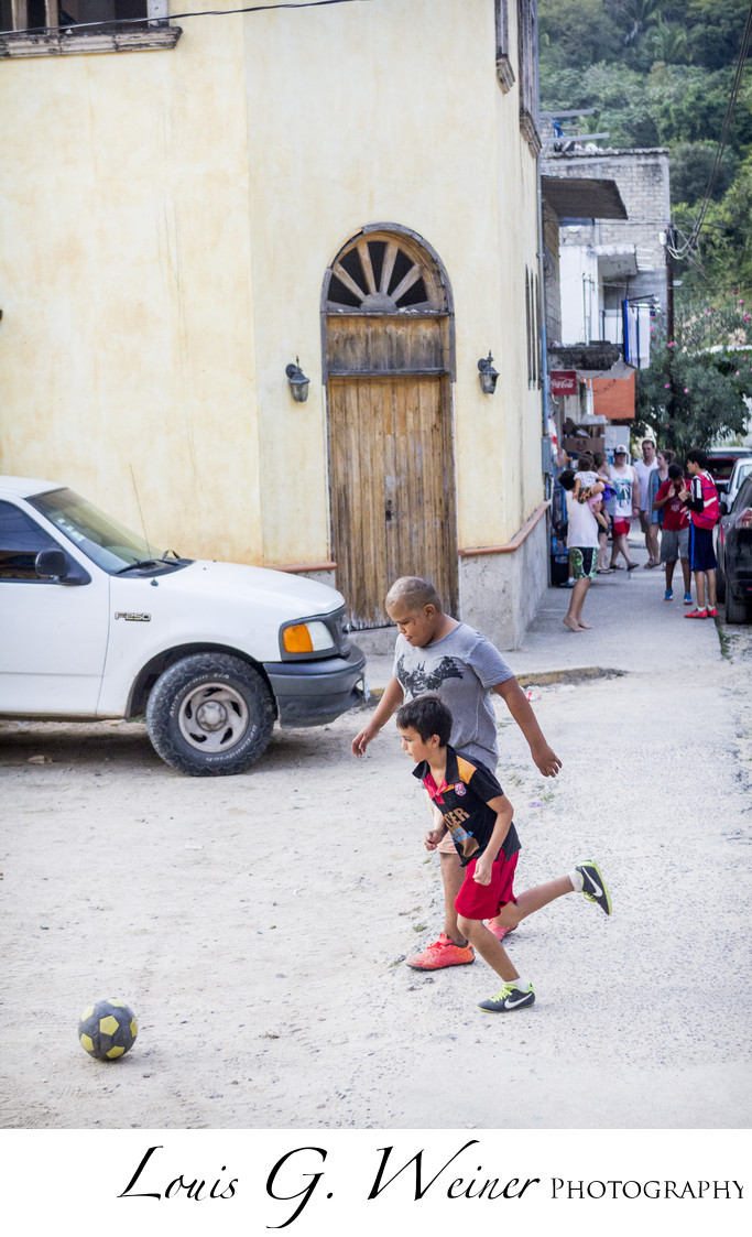 Puerto Vallarta Mexico, kids playing football in the street.