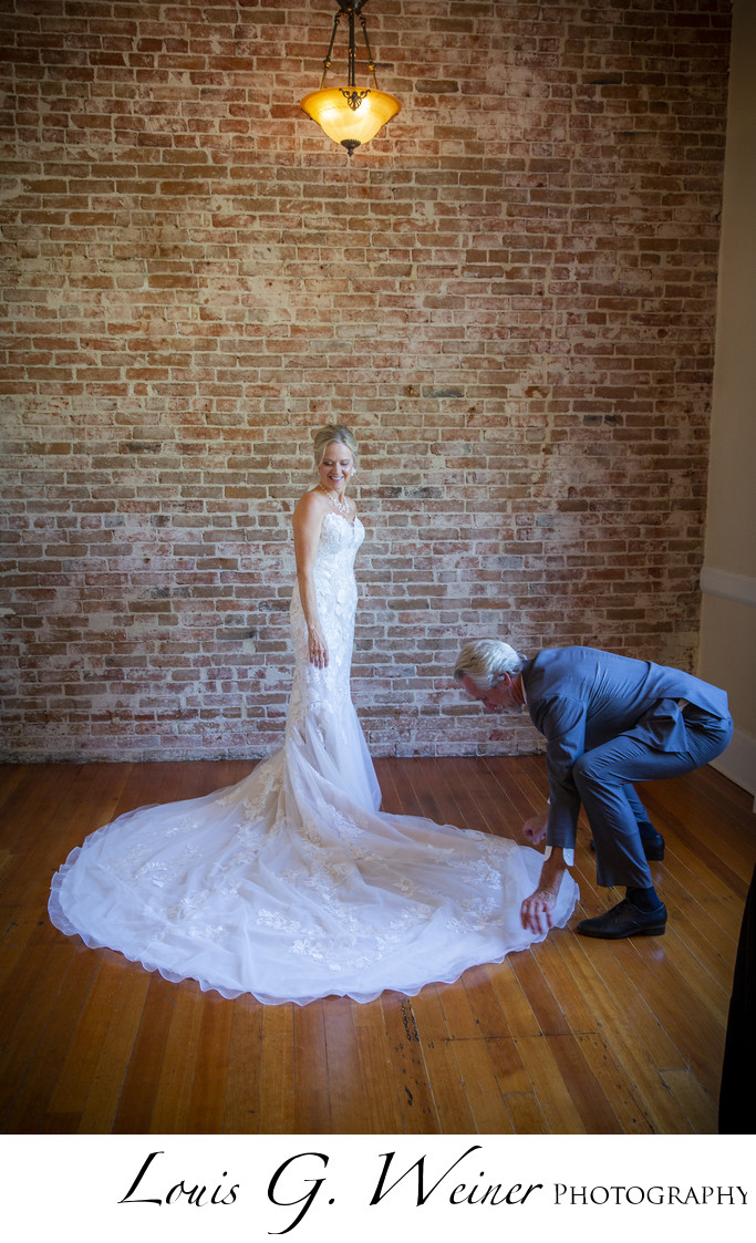 Groom helping his new bride with her dress train