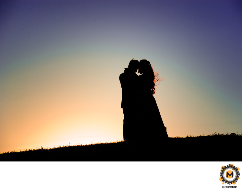 Silhouetted Couple Embracing on Hill with Sunset