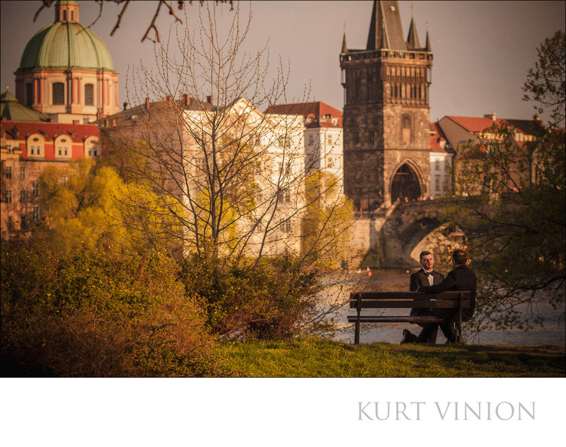 Two men in tuxedos near the Charles Bridge