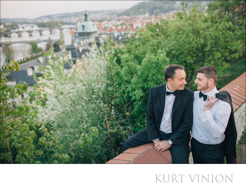 Two men in tuxedos sharing a moment overlooking Prague