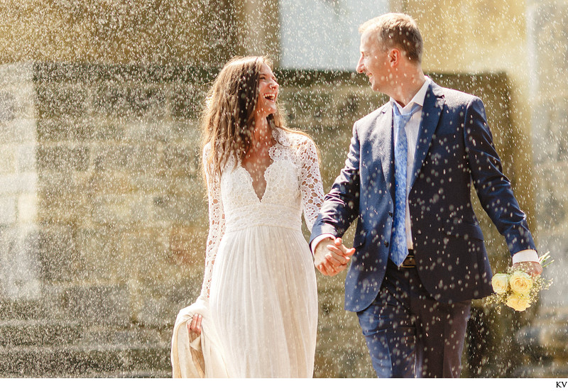 Happy couple water sprinkler Prague wedding photography