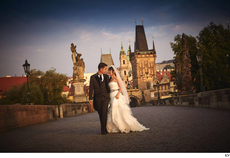 walking on deserted Charles Bridge on wedding day