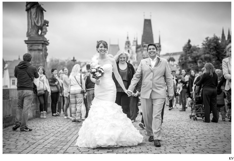the happy couple walking hand in hand Charles Bridge
