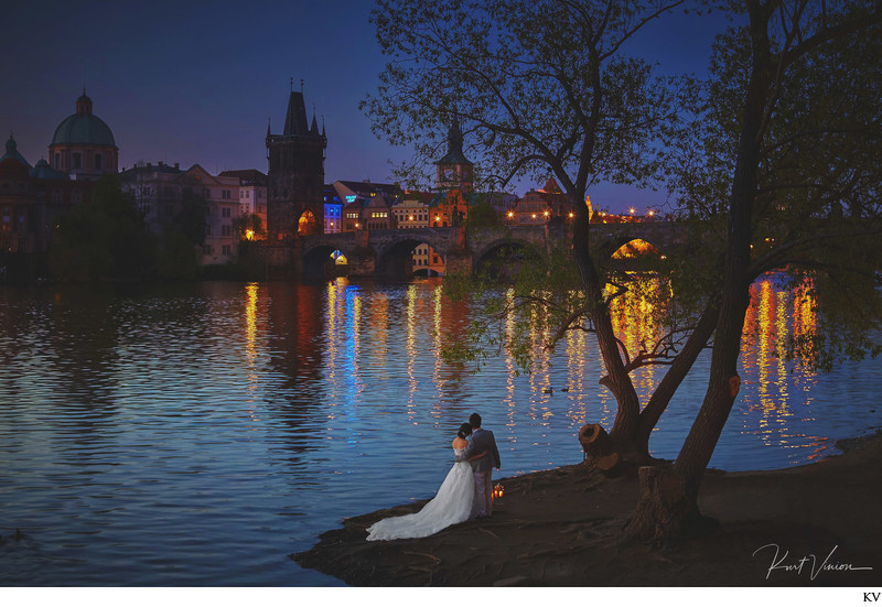 twilight lovers snuggling near Charles Bridge Prague