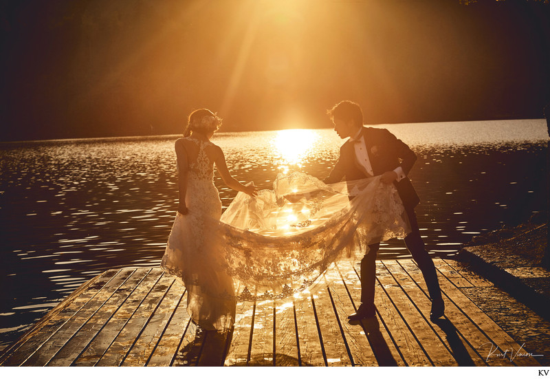 helping brides veil in the Golden Light of Lake Bled