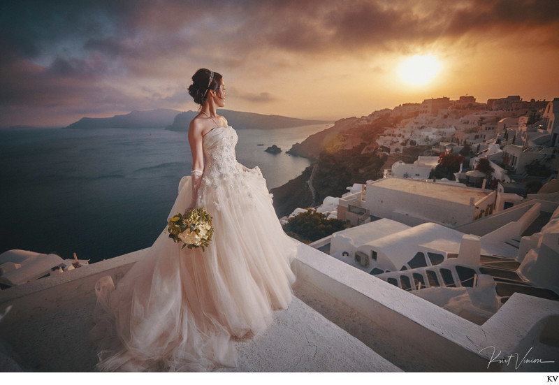 Bride watching sunset over Santorini on her wedding day