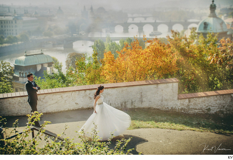 twirling bride as groom watches above Prague