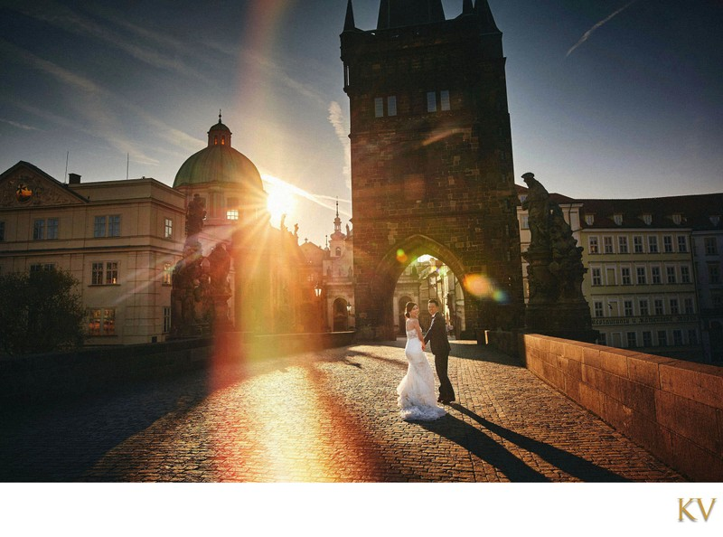 bride & groom running across Charles Bridge at sunrise