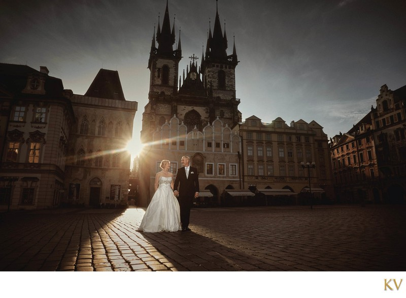 wedded couple walking in Prague's Old Town at sunrise