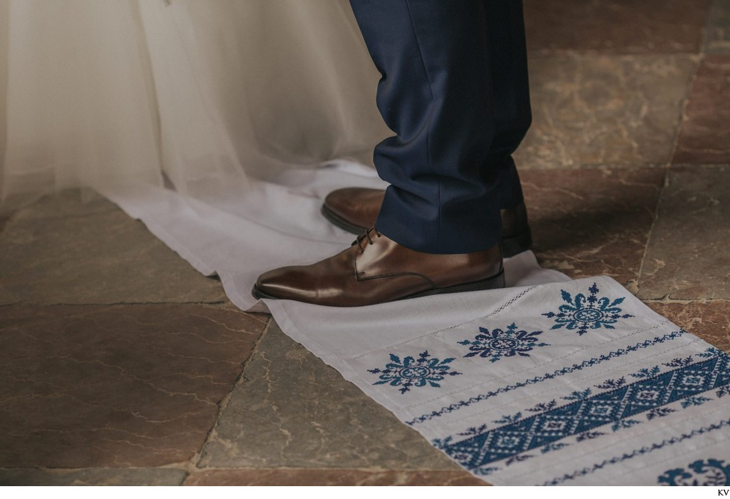 The groom stands on a cloth during his wedding day