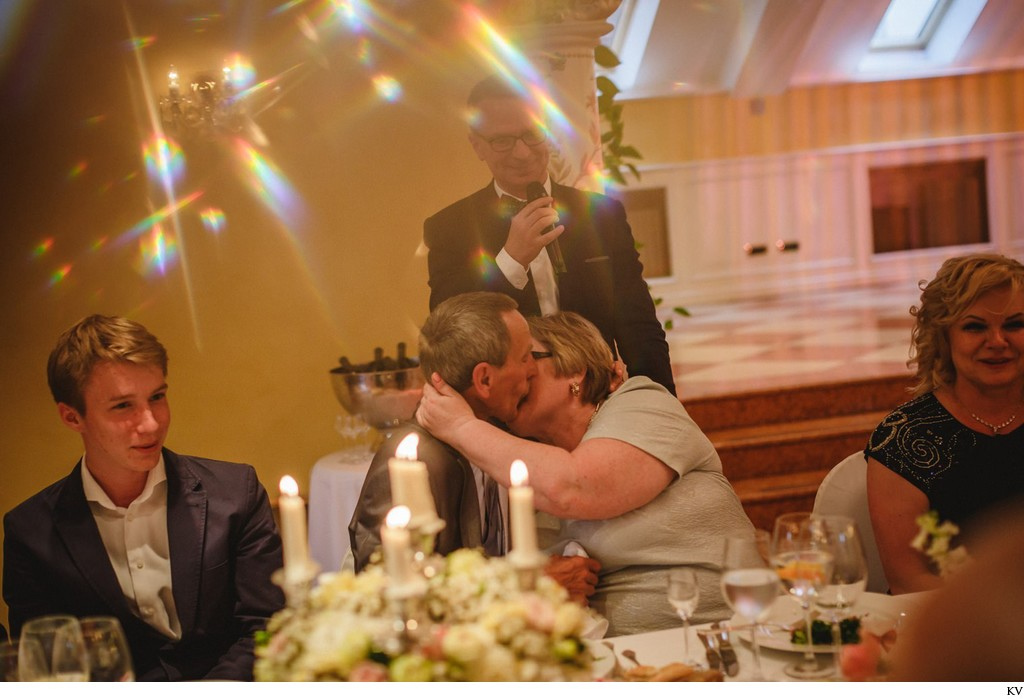 The brides parents kiss at the wedding dinner
