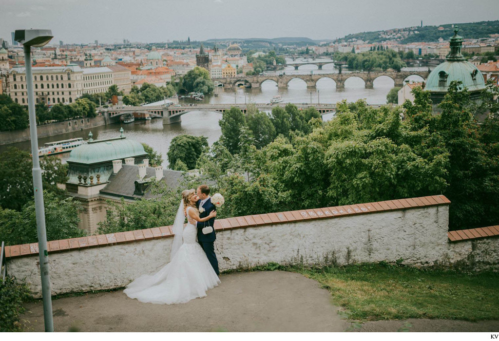 Gorgeous wedding couple embracing above Prague
