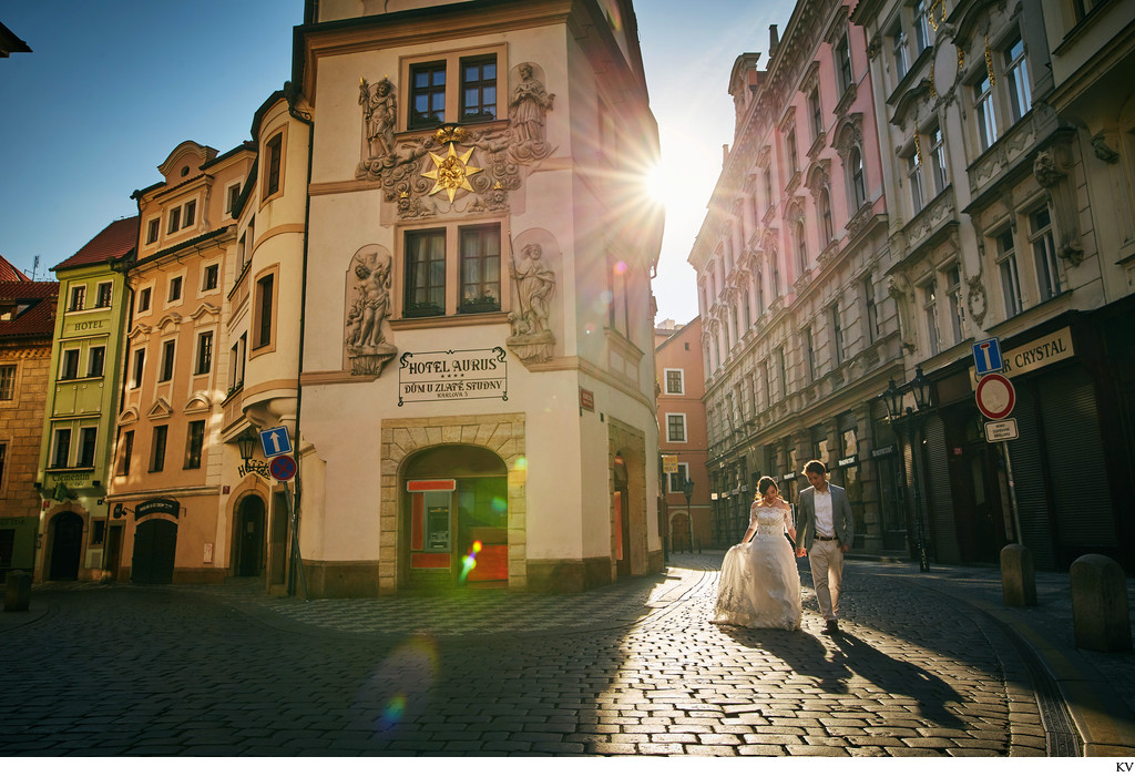 sun flare leads a couple in the Old Town of Prague