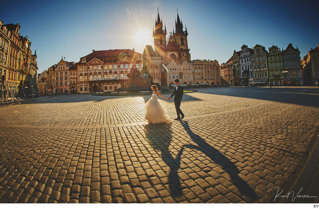 walking hand in hand at sunrise Old Town Square Prague