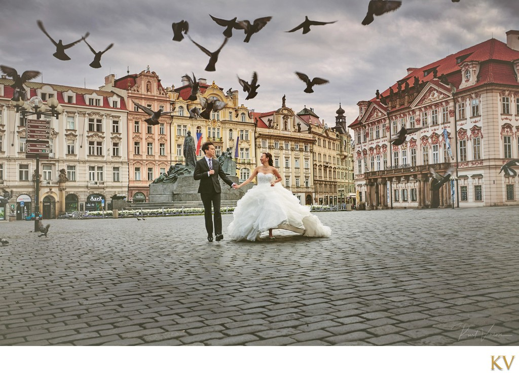 wedding couple running through deserted Old Town Square