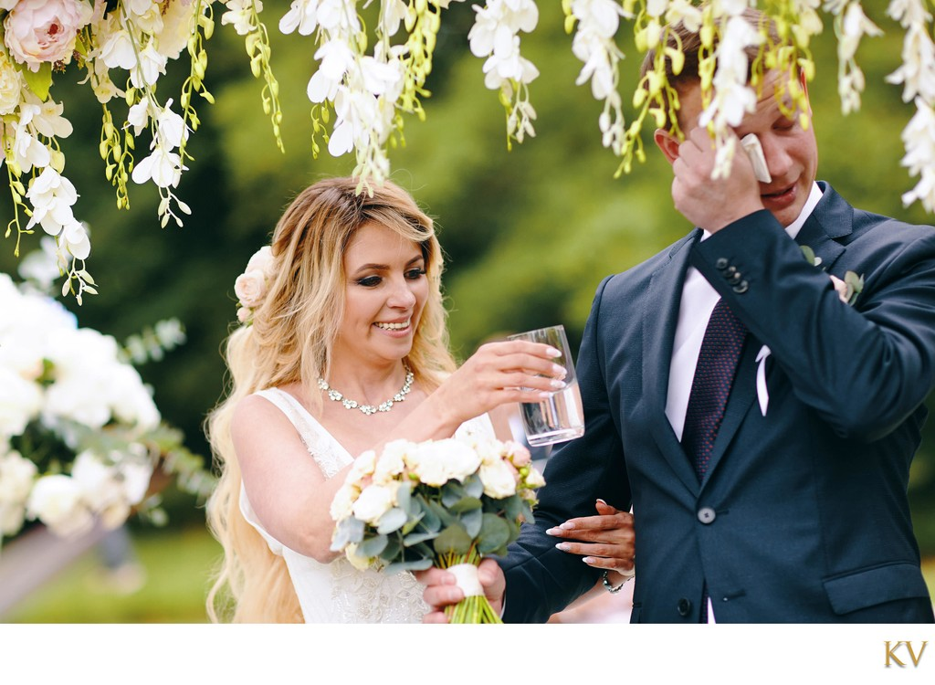 bride gives water to teary eyed groom during ceremony