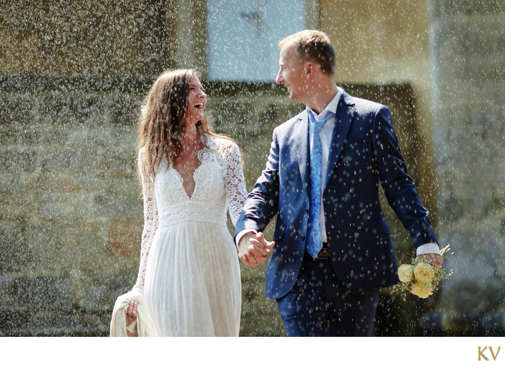 Newlweds walking through sprinkler at Prague Castle