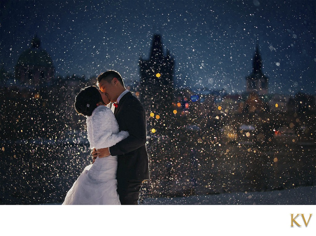 bride & groom kissing at night in a snowstorm in Prague