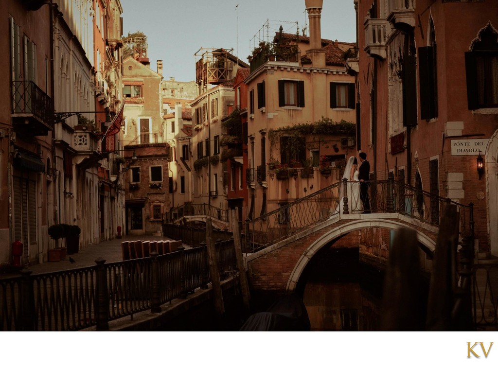 wedded couple watching sunrise over canals of Venice