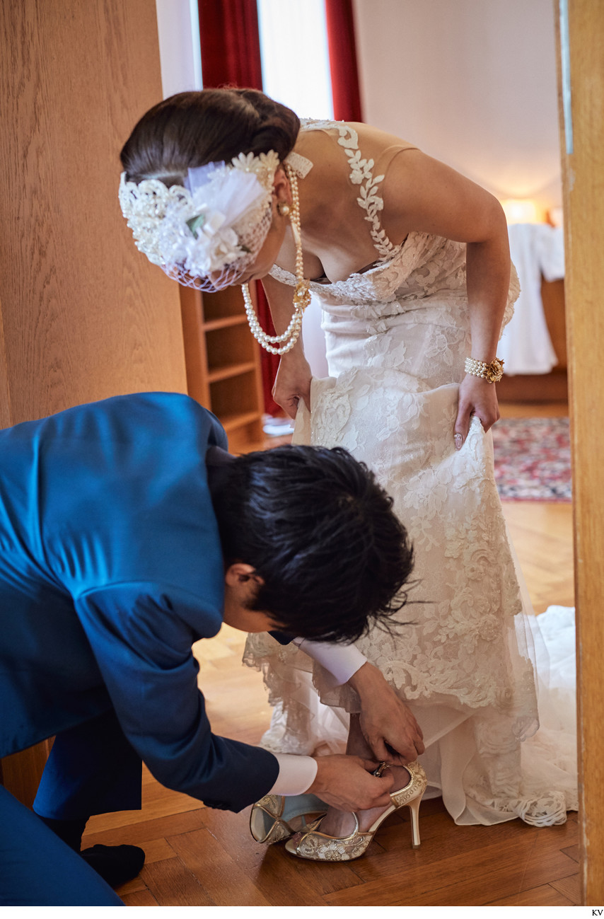 groom helps bride with shoes I Vila Bled Weddings