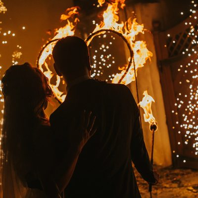 newlyweds watch as a heart burns in their honor