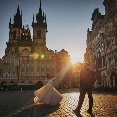 bride twirling her dress in Old Town Square at sunrise