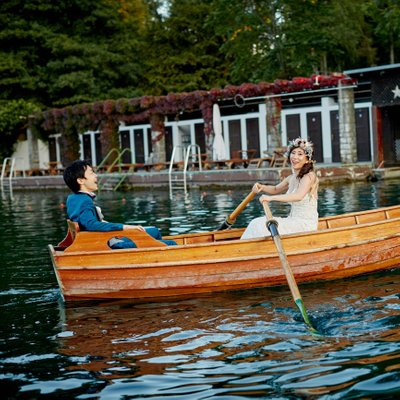 Bride rowing  the boat as groom laughs