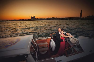 Thai couple in boat enjoying sunset over Venice
