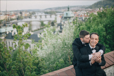 A kiss for his partner overlooking Prague
