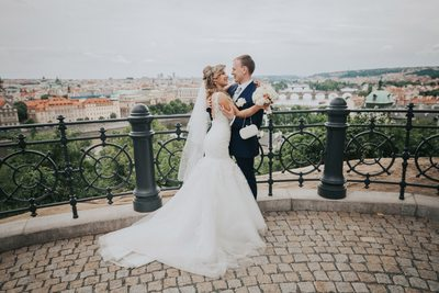 bride & groom embracing above Prague on wedding day