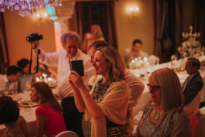 wedding guests take pictures during the party