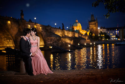 elegant couple enjoying moment Charles Bridge nite