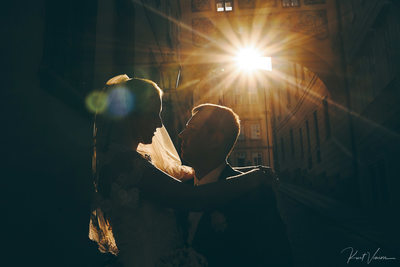 magical sunlight flares around wedding couple Prague