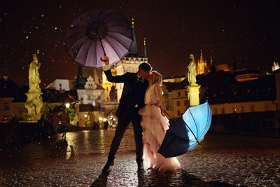Kissing in the rain under umbrellas Charles Bridge