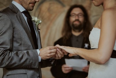 placing the wedding band on his brides finger