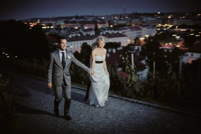 Excited bride led by groom into vineyards above Prague