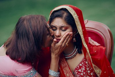 tearful Indian bride caressed by her mother
