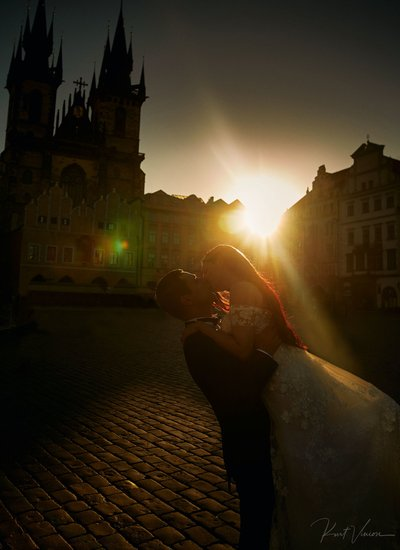A kiss for the bride in the Old Town Square at sunrise