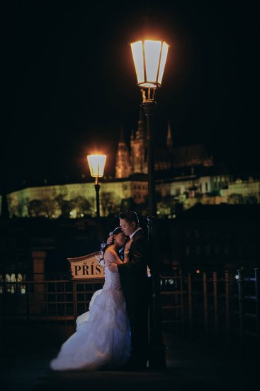 A couple embrace underneath a gas lamp in Prague