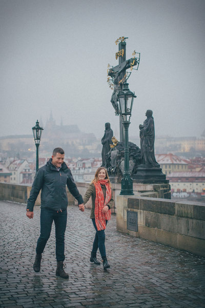 newly engaged happily walking across the Charles Bridge