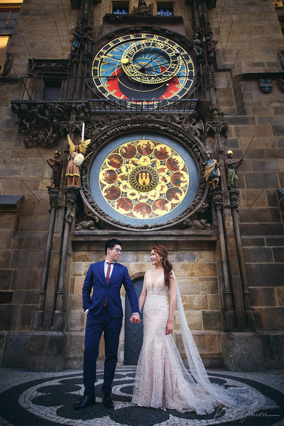 Gorgeous couple standing under the Prague Orloj