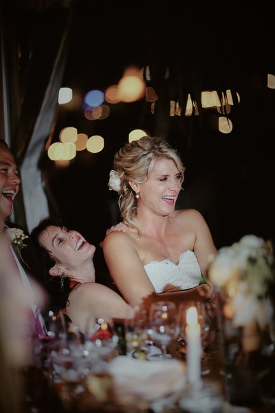 happy bride sitting in bridesmaids lap