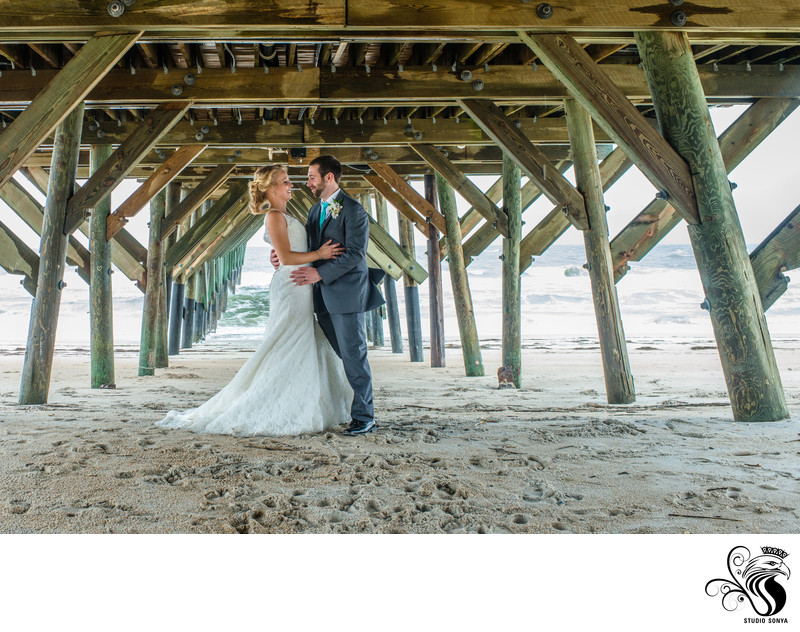 Groom and Bride under the pier at Wrightsville Beach