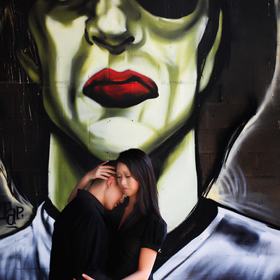 Engagement portrait in front of mural
