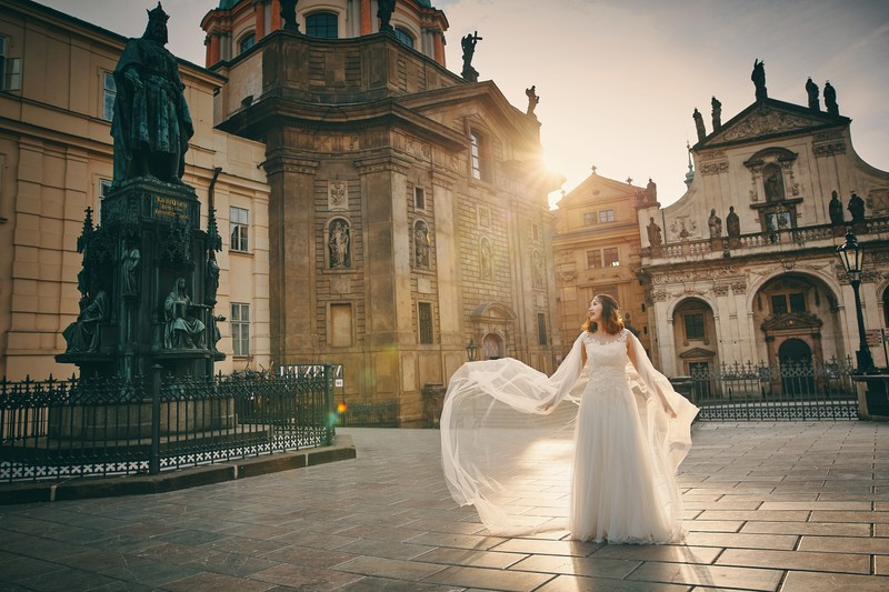 a bride fluffs her veil as the sun flares around her