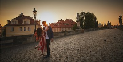 sharing a moment on the Charles Bridge at sunrise