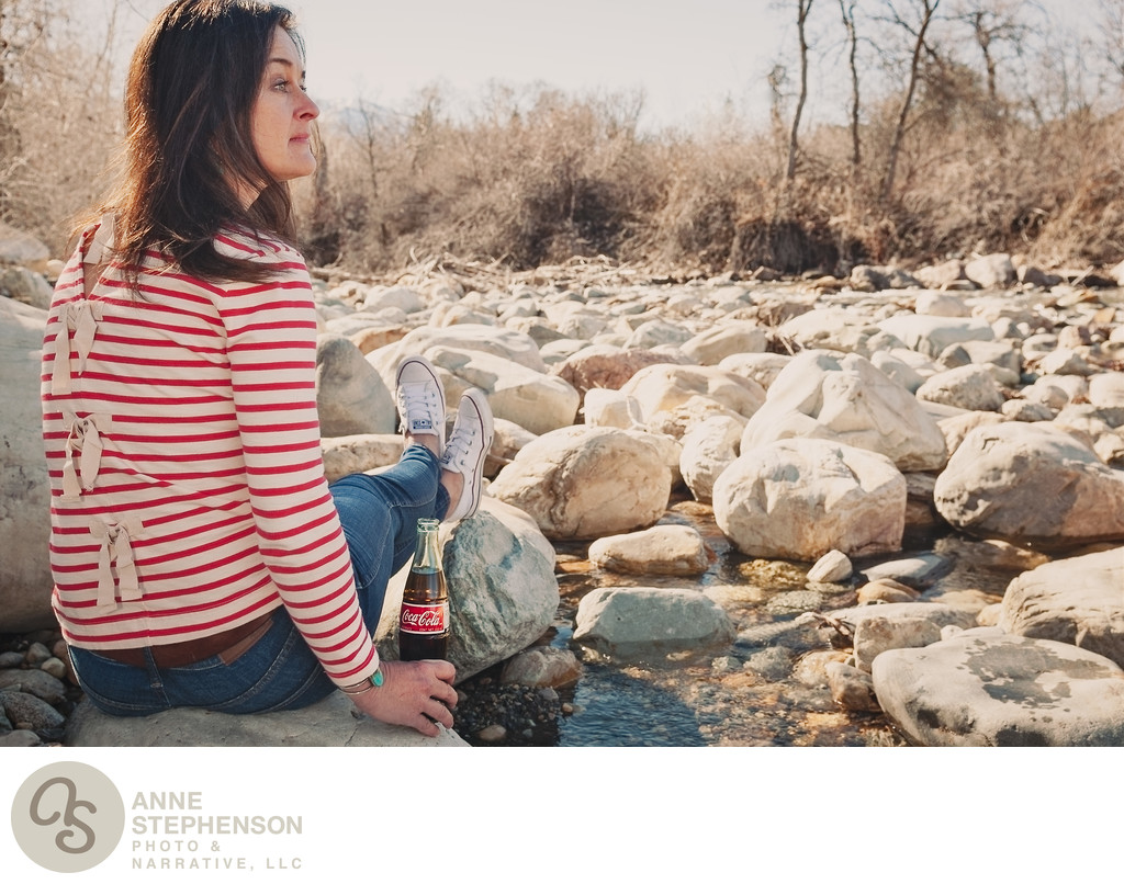 Woman with Coca Cola bottle at edge of a rocky creek