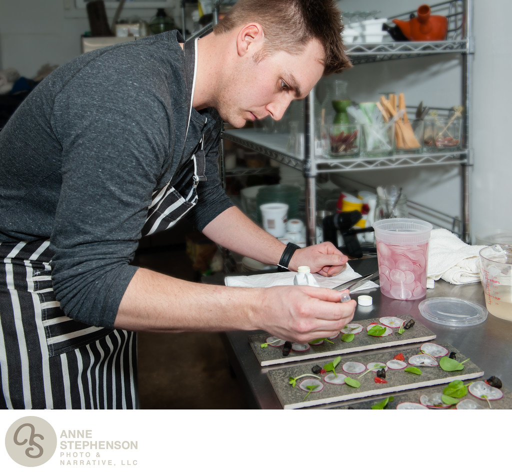 Chef applies microgreens with tweezer
